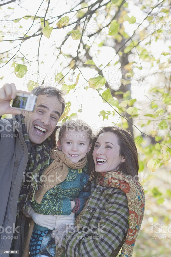Family taking self-portrait outdoors in autumn stock photo