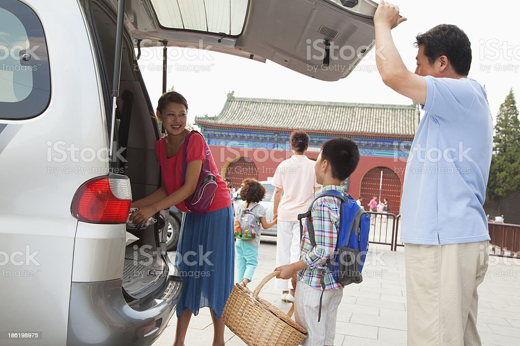 Family taking stuff out from the car, preparing for picnic royalty-free stock photo