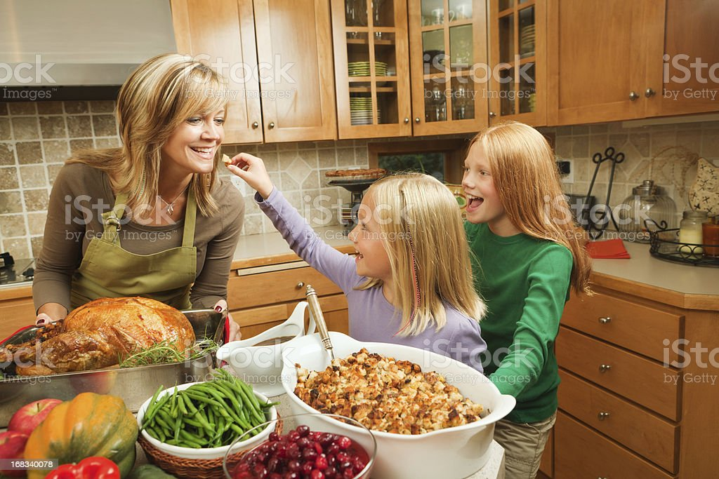 Family Thanksgiving with Mother, Daughters Cooking Holiday Dinner in Kitchen stock photo