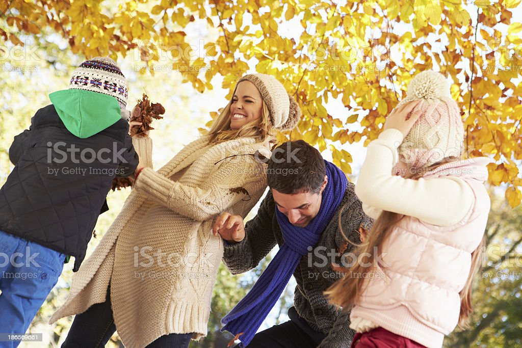 Family Throwing Leaves In Autumn Garden royalty-free stock photo