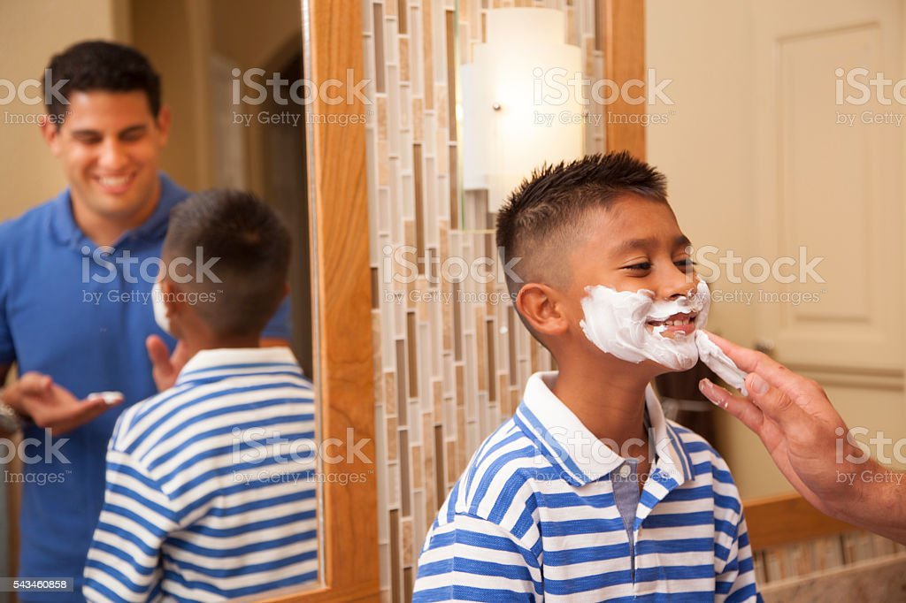 Family Time!  Single dad and son 'shaving' in home bathroom. stock photo