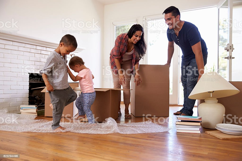Family Unpacking Boxes In New Home On Moving Day stock photo