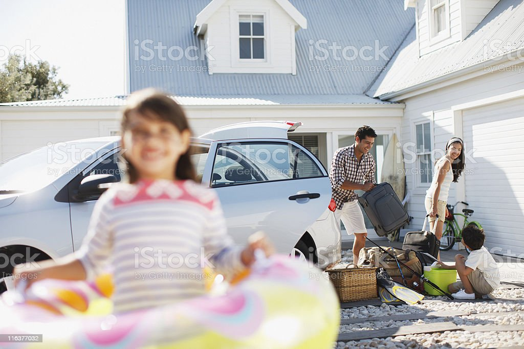 Family unpacking car in driveway royalty-free stock photo