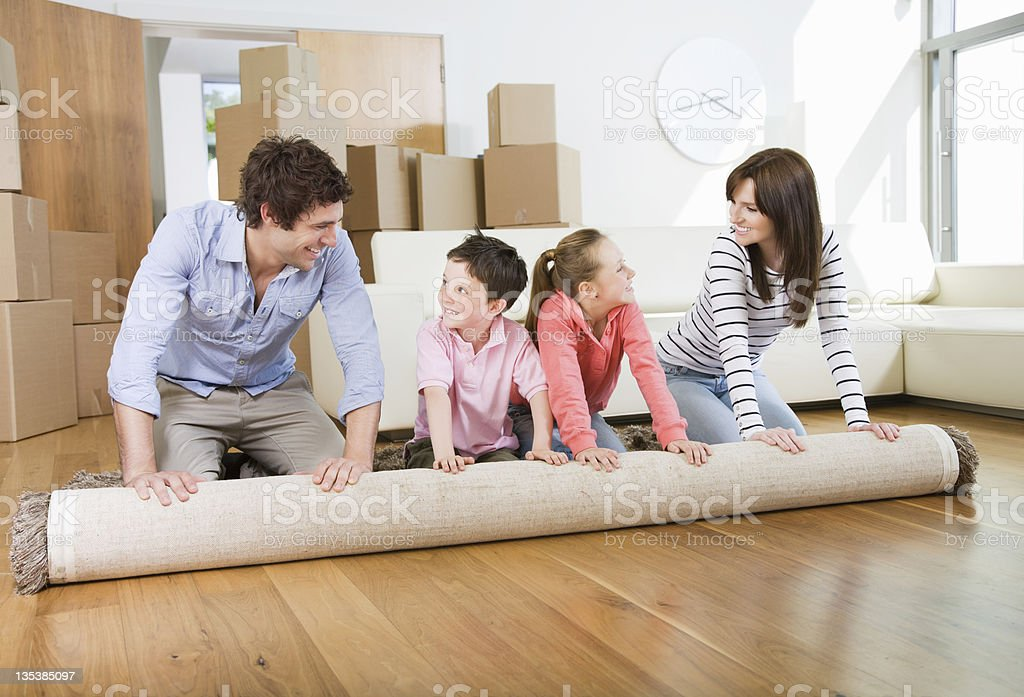 Family unrolling carpet together in new home stock photo