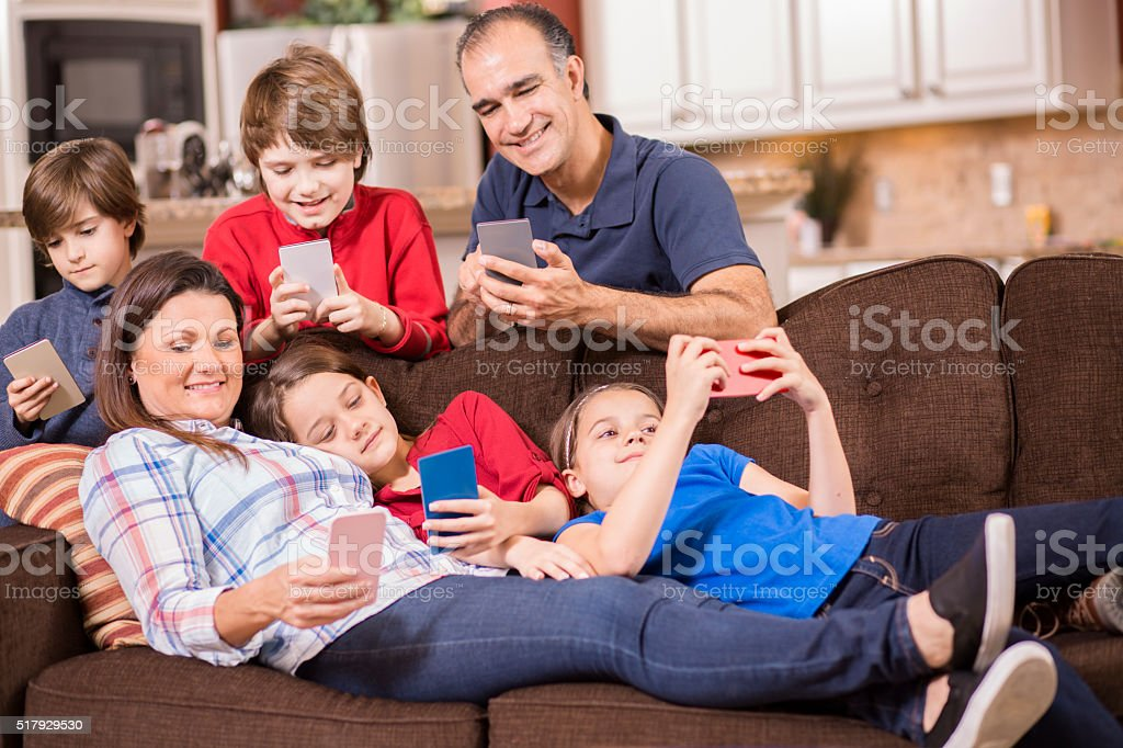 Family using cell phones at home.  Children, parents.  Technology. stock photo