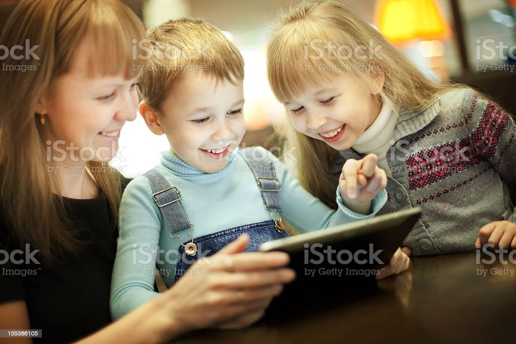Family using digital tablet in cafeteria royalty-free stock photo