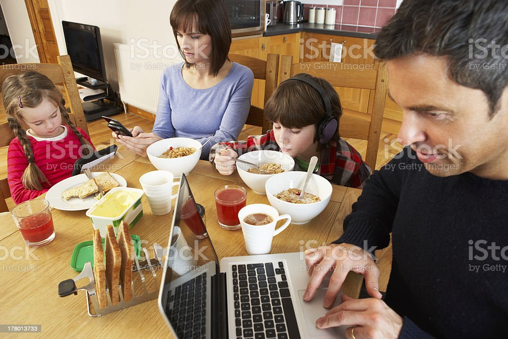 Family Using Gadgets Whilst Eating Breakfast Together In Kitchen stock photo
