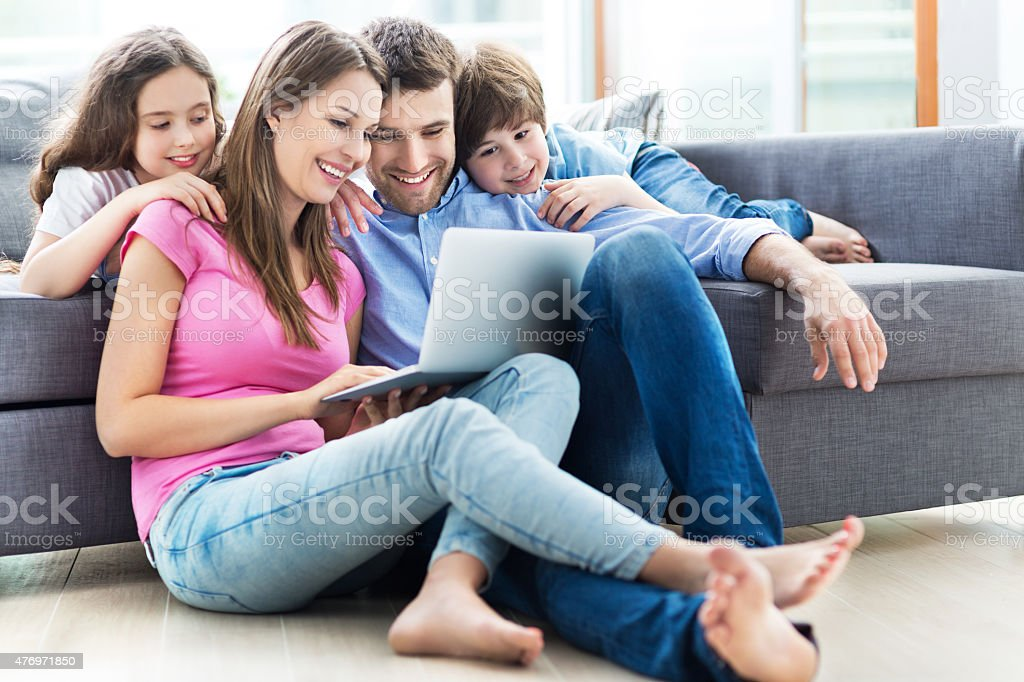 Family using laptop at home stock photo