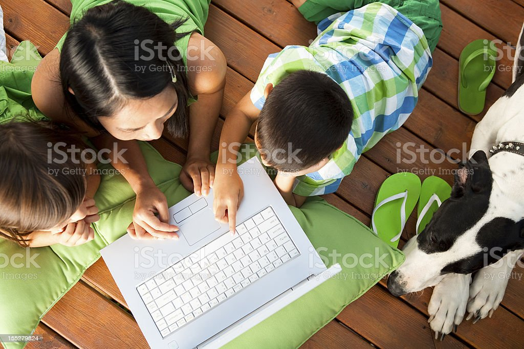 Family using laptop on deck royalty-free stock photo