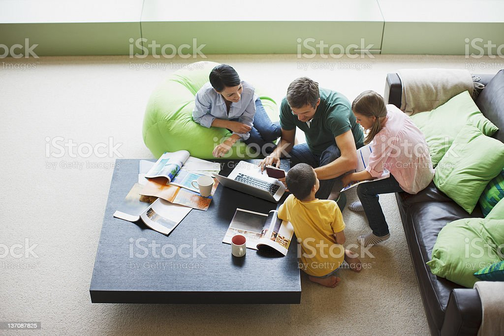 Family using laptop together in living room stock photo