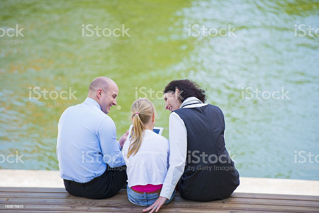Family Using Tablet Outdoors On A Bench royalty-free stock photo