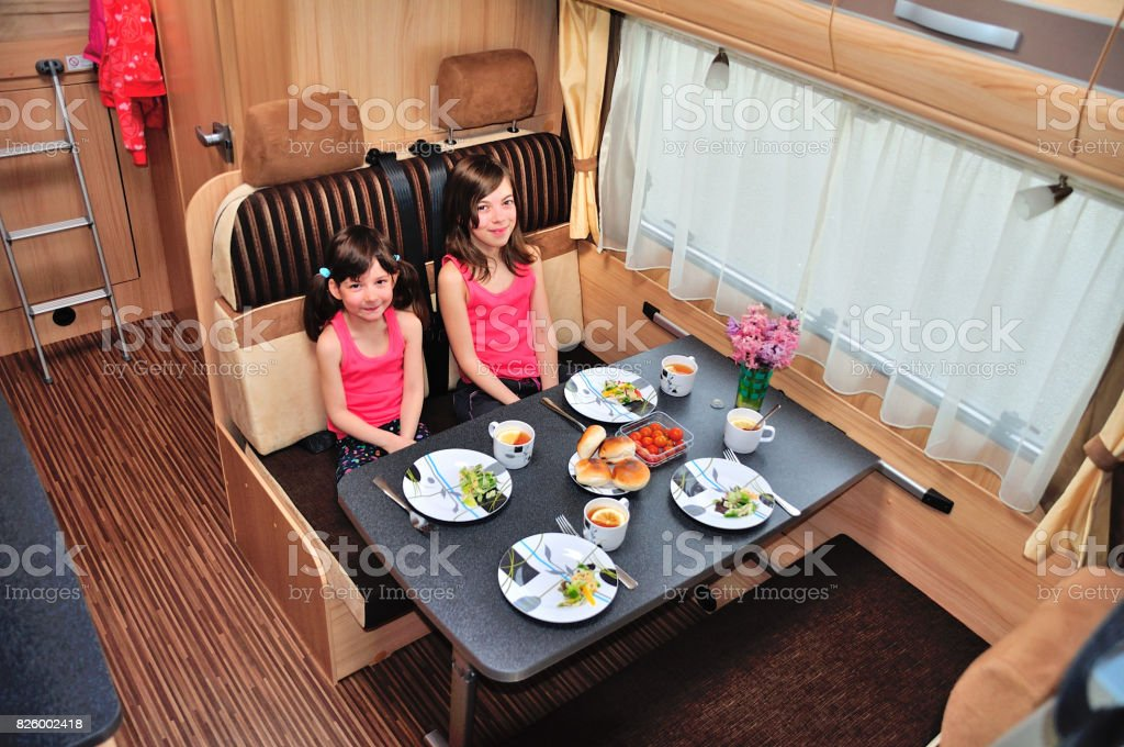 Family vacation RV holiday trip, happy smiling kids travel on camper, children in motorhome interior stock photo