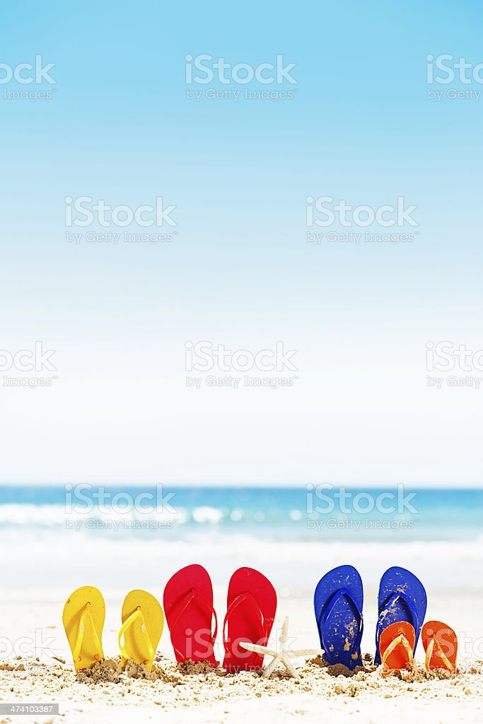 Family vacation time: four pairs of flipflops on summer beach royalty-free stock photo