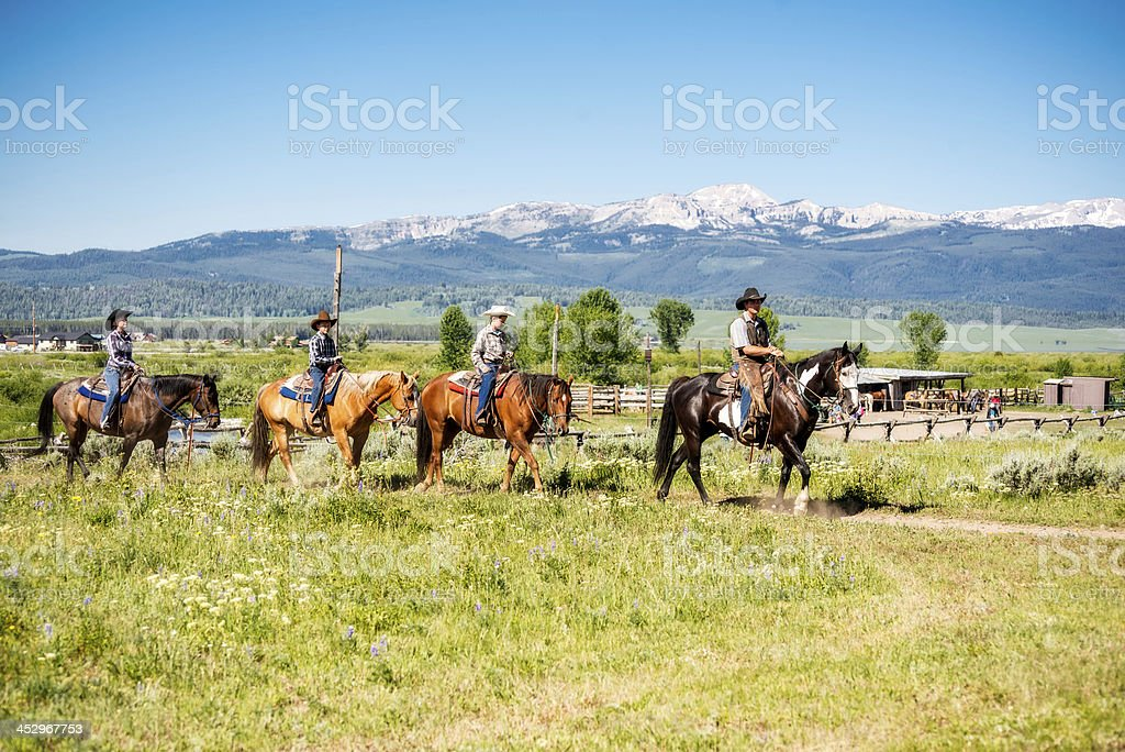 Family Vacationing on Horse Back at Dude Ranch in Montana stock photo