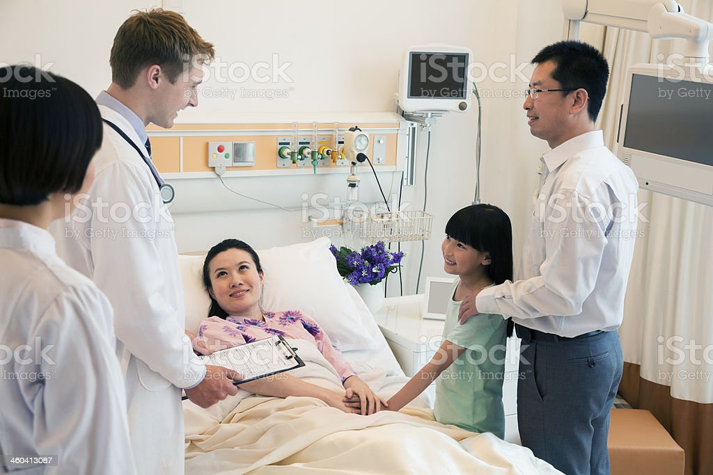 A family visiting a mother in the hospital stock photo