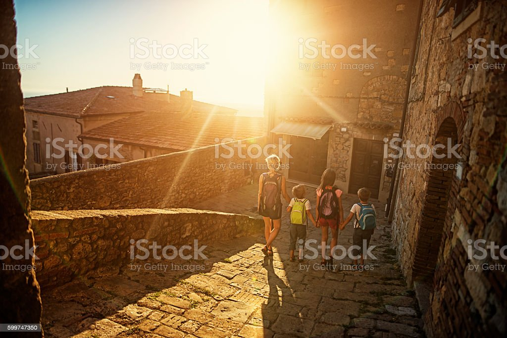 Family visiting charming Italian town in Tuscany stock photo