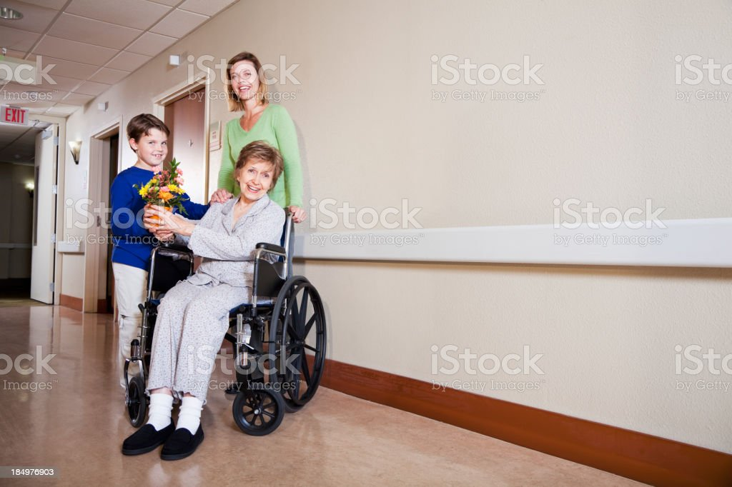 Family visiting elderly woman in hospital royalty-free stock photo