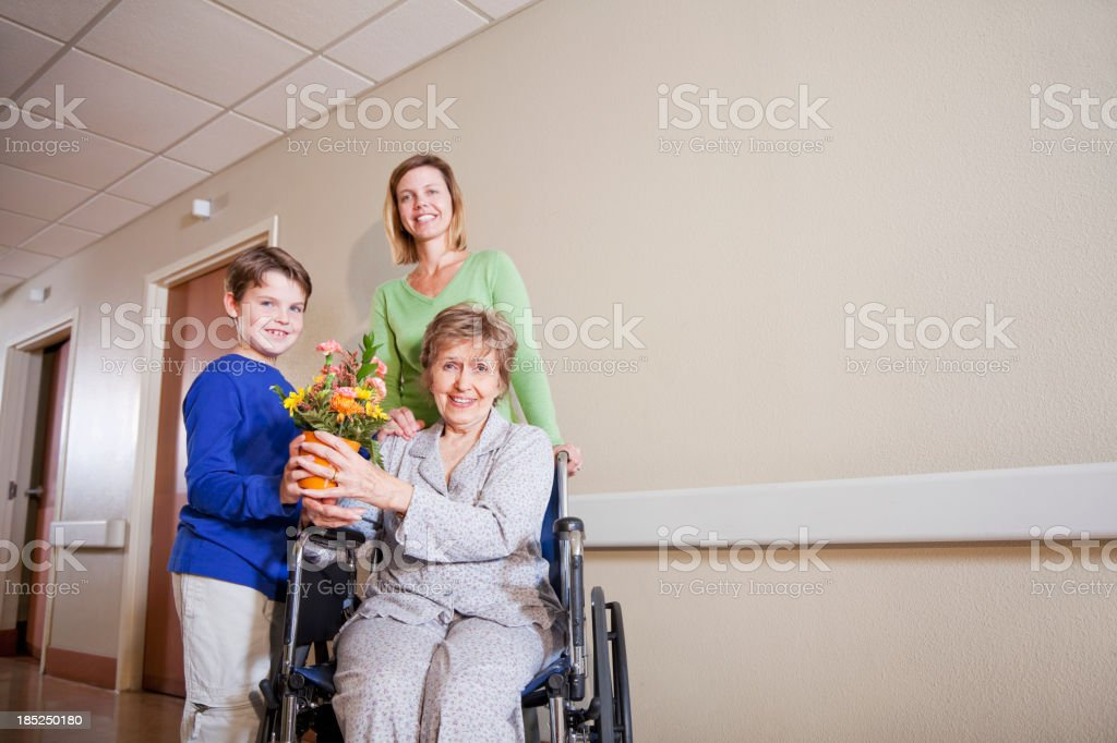 Family visiting elderly woman in hospital stock photo