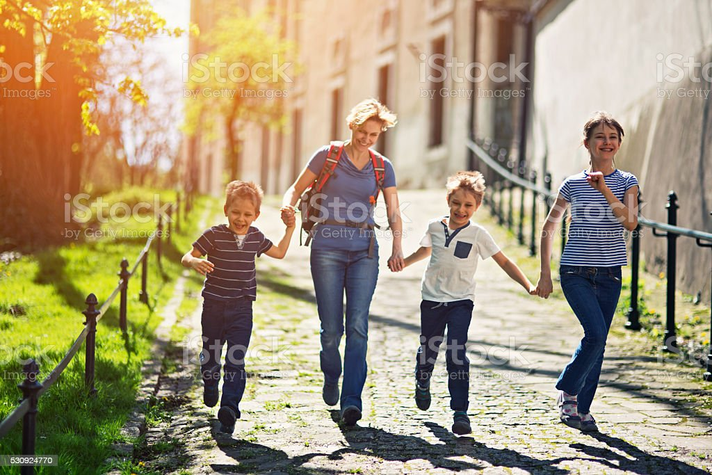 Family visiting Krakow running in old town stock photo
