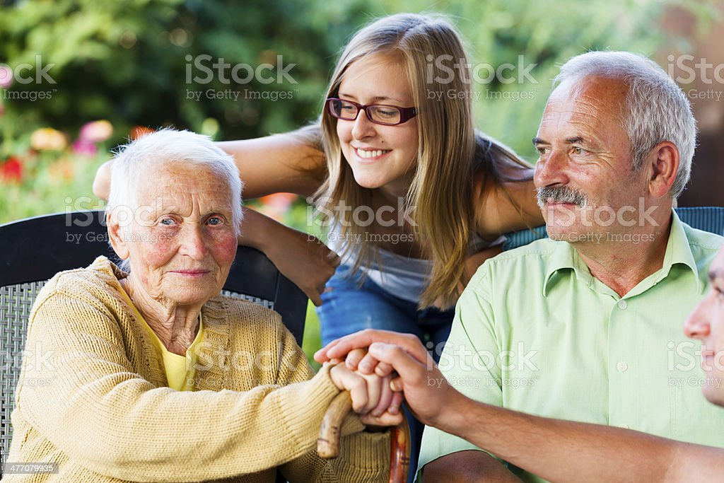 Family Visiting Sick Grandmother in Nursing Home stock photo