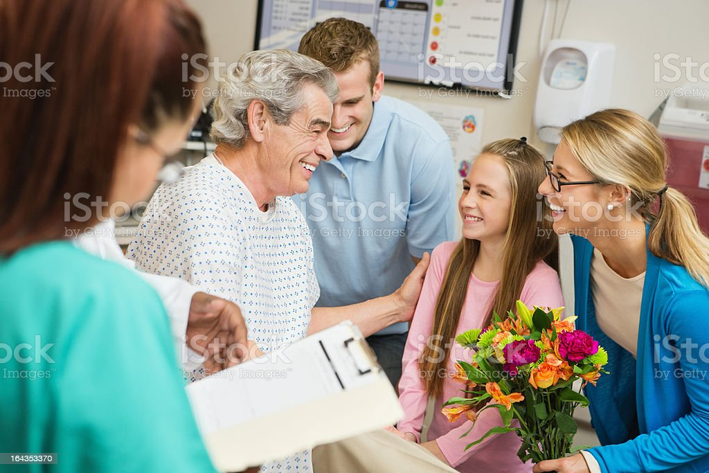 Family visiting with sick grandfather in hospital, nurse checking chart royalty-free stock photo