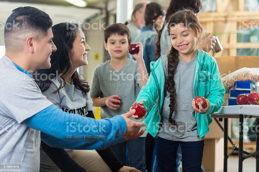 Family volunteers at food bank stock photo