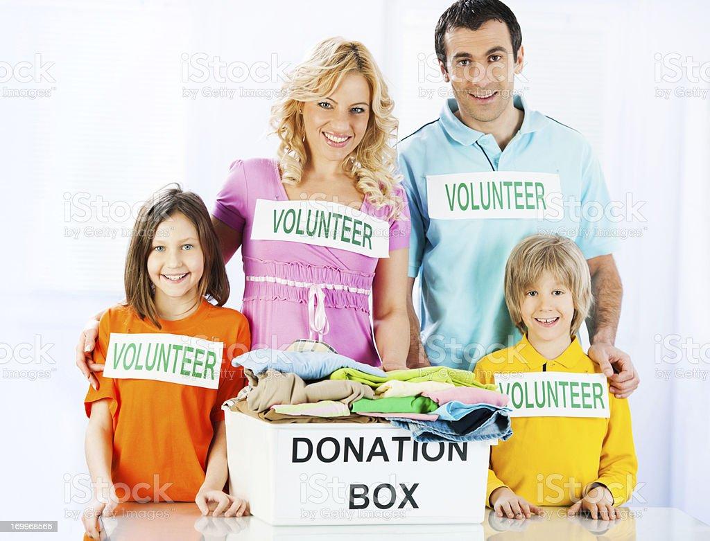 Family volunteers standing near full donation box. royalty-free stock photo