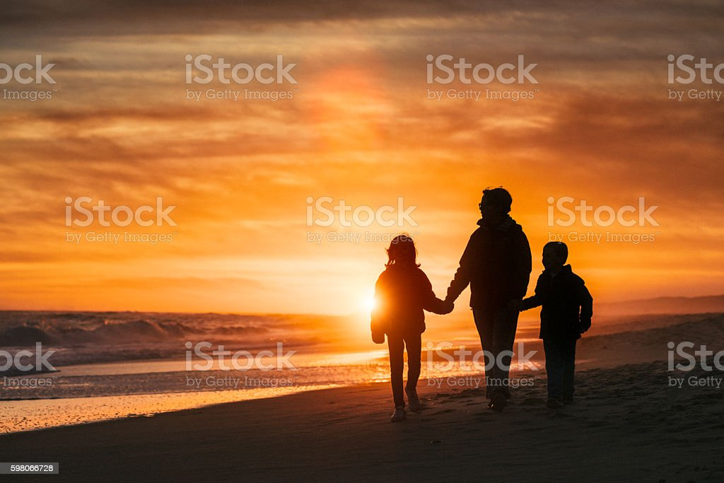 Family walk by the beach at sunset stock photo