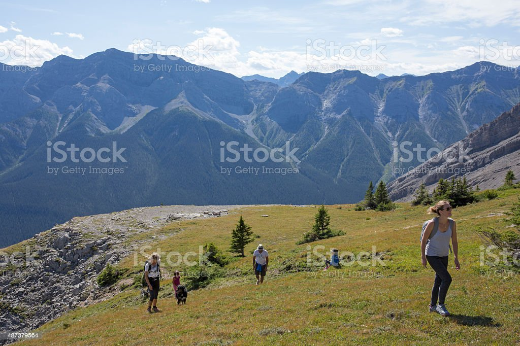 Family walk up alpine slope above mountains, valley stock photo