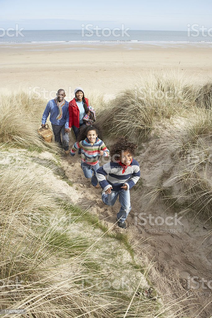 Family Walking Along Dunes On Beach royalty-free stock photo