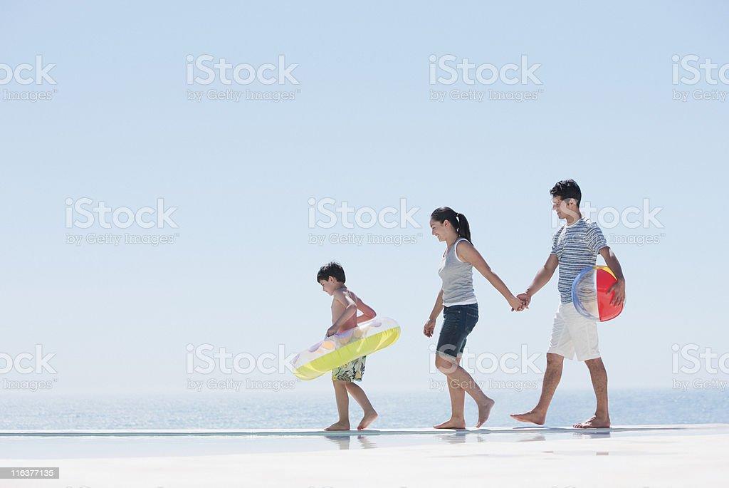 Family walking along infinity pool royalty-free stock photo