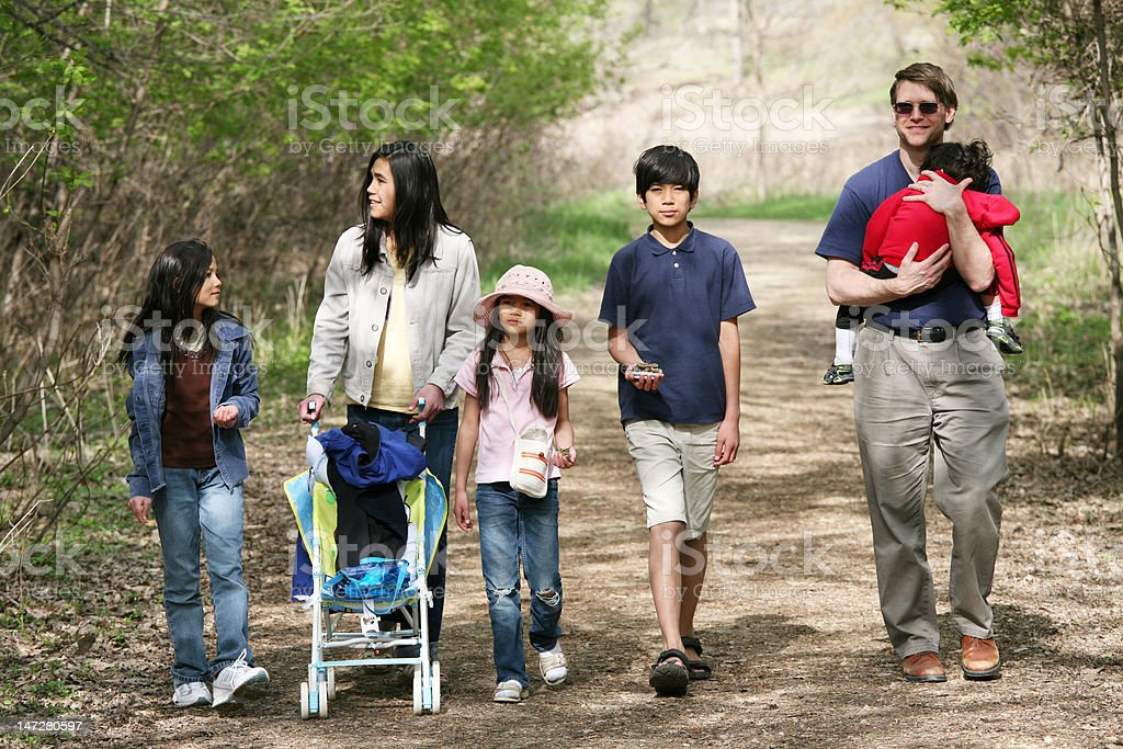 Family walking along quiet country path stock photo