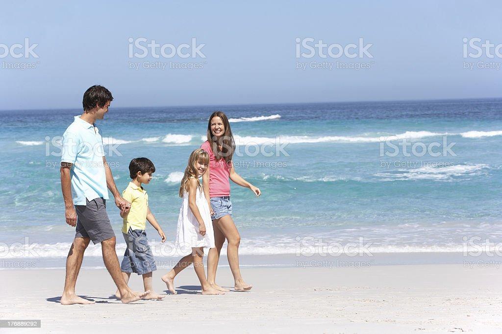 Family Walking Along Sandy Beach stock photo