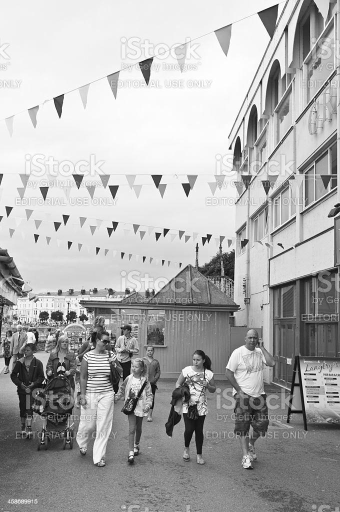 Family walking along seaside promenade under flags royalty-free stock photo