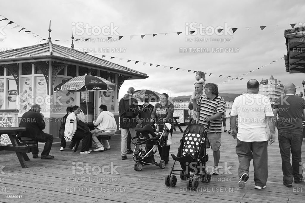 Family walking along traditional wooden seaside pier royalty-free stock photo