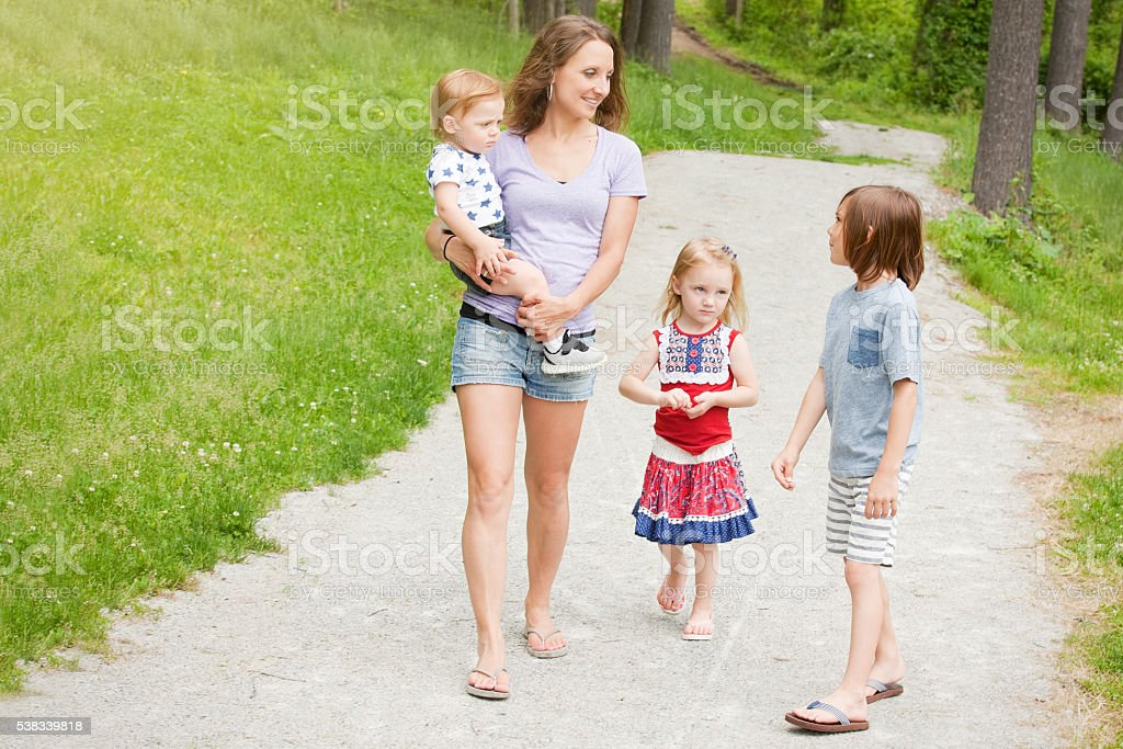 Family Walking And Talking In Park stock photo
