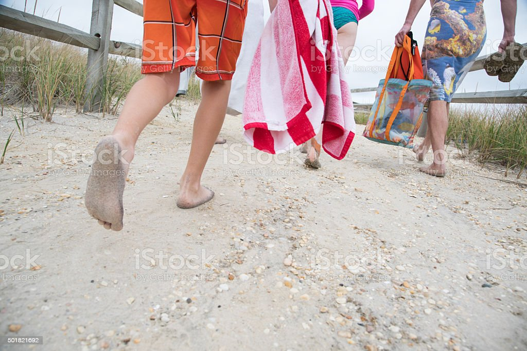 Family walking barefoot on a Beach Path stock photo
