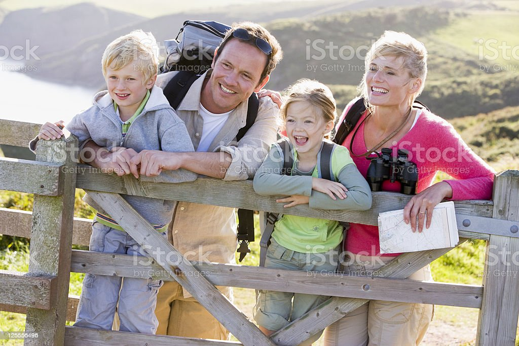 Family walking cliffside path leaning on fence stock photo