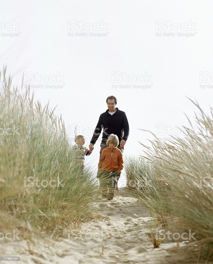 Family walking down a dune royalty-free stock photo