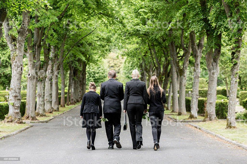 Family walking down alley at graveyard stock photo
