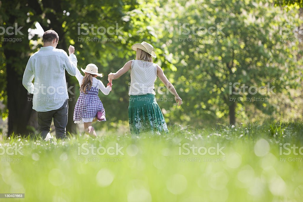 Family walking hand-in-hand in park stock photo