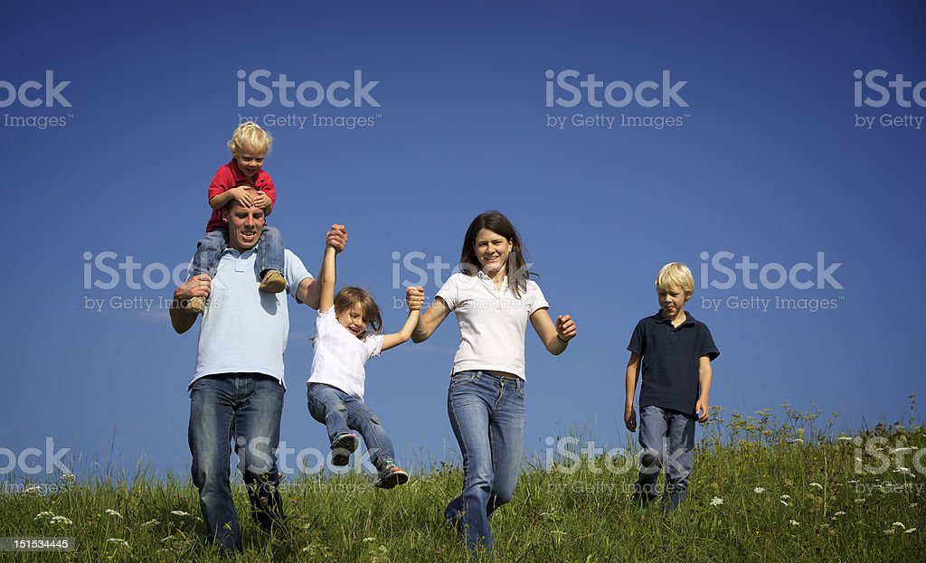 Family walking in field playing with children royalty-free stock photo