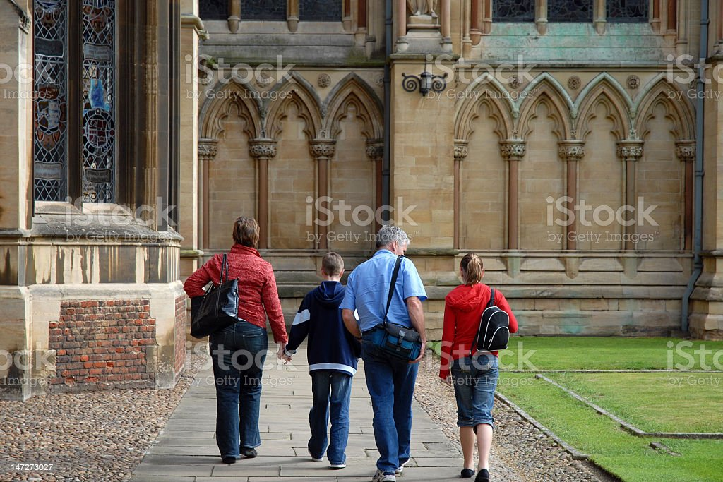 A family walking in the gardens of the church royalty-free stock photo