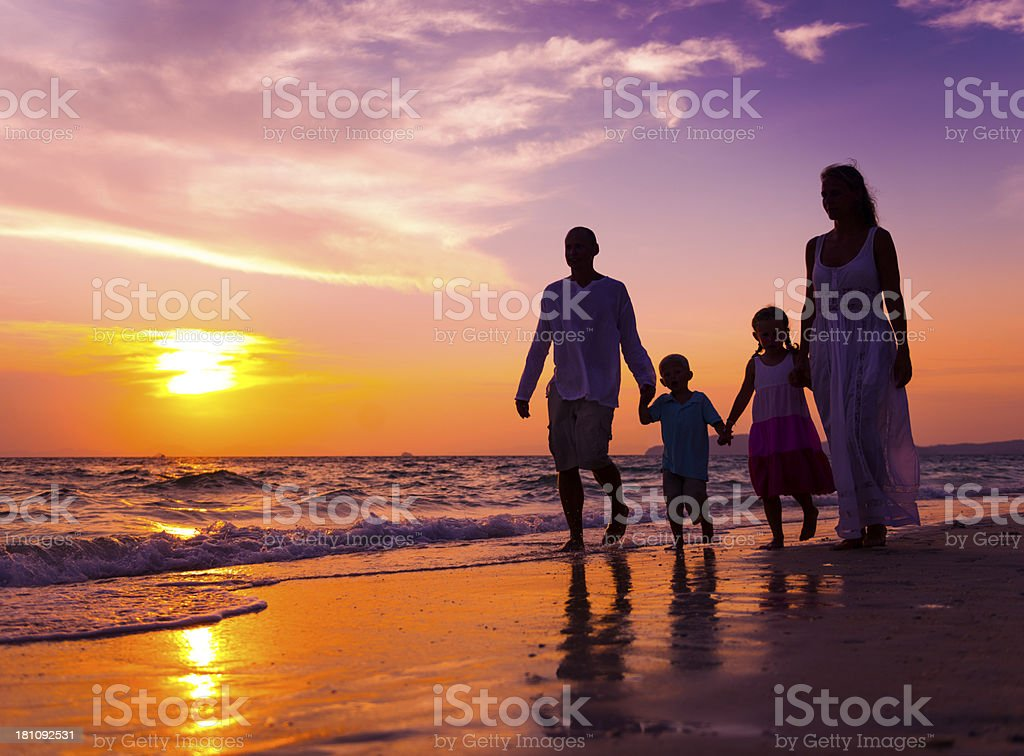 Family walking on a beach at sunset stock photo
