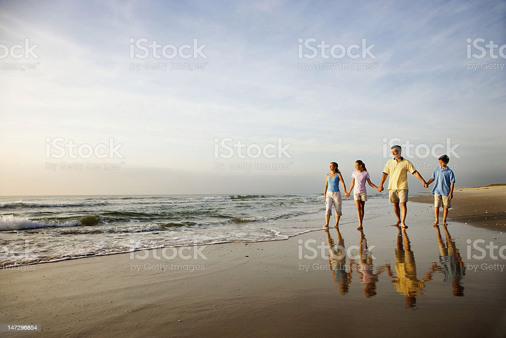 Family walking on the beach royalty-free stock photo