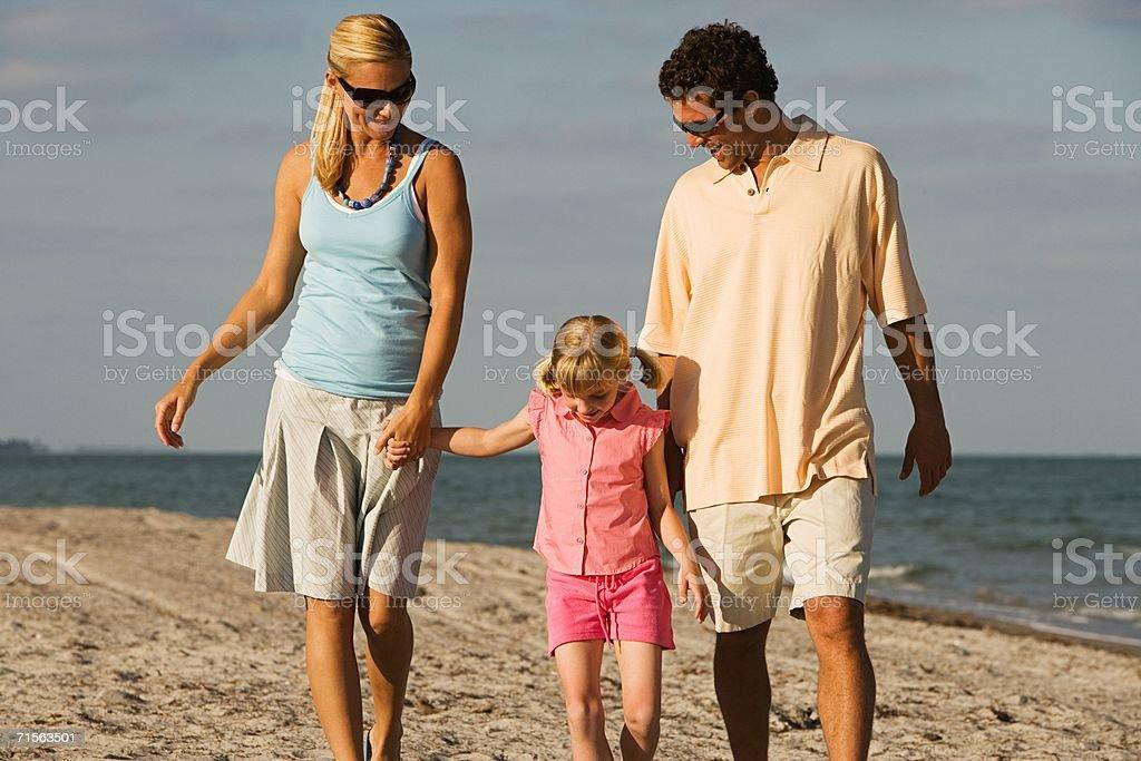 Family walking on the beach royalty-free stock photo
