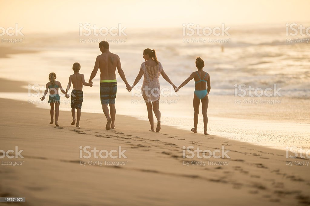 Family Walking on the Beach Together stock photo