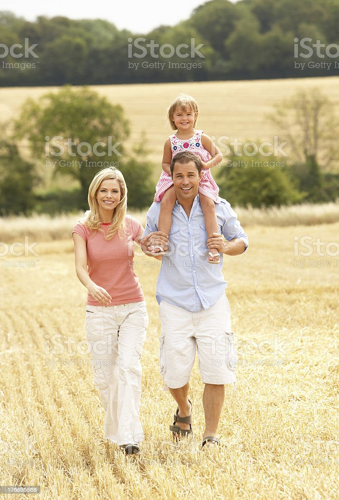 Family Walking Through Summer Harvested Field royalty-free stock photo