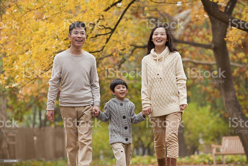 Family walking through the park in autumn stock photo