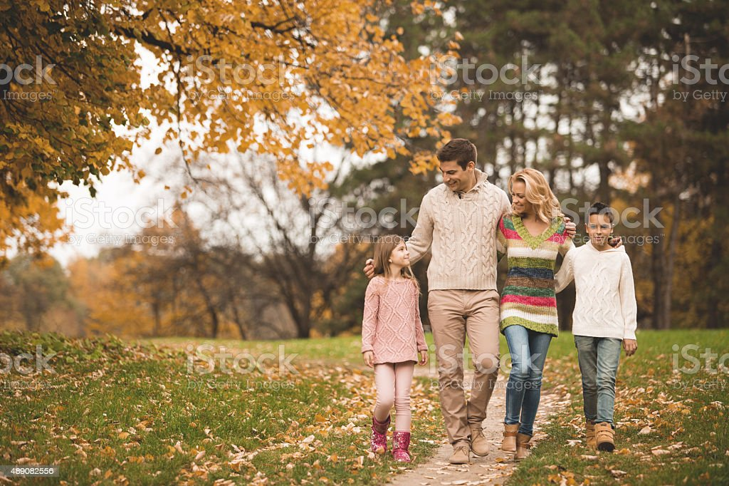 Family walking through the park in the autumn stock photo